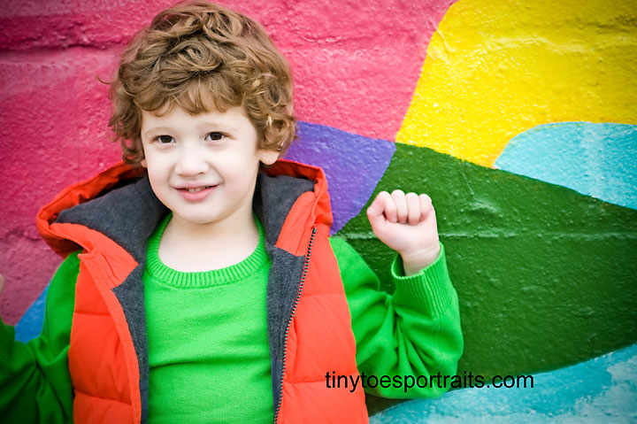 little boy in front of very colorful wall