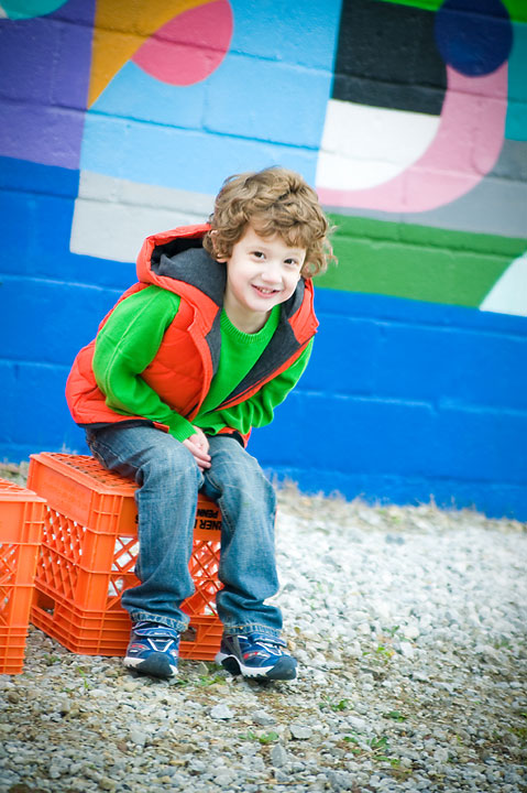 boy on crates in front of colorful wall