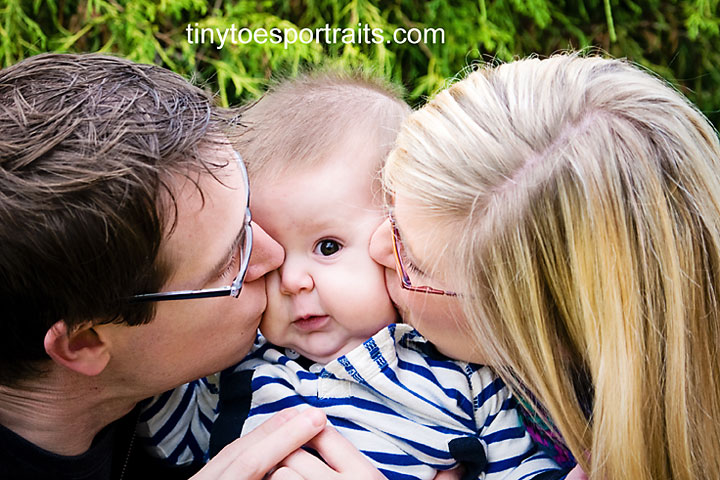 portrait of baby boy being kissed on both cheeks by his parents