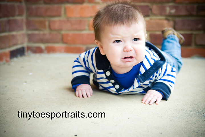 portrait of baby boy crying lying on his belly