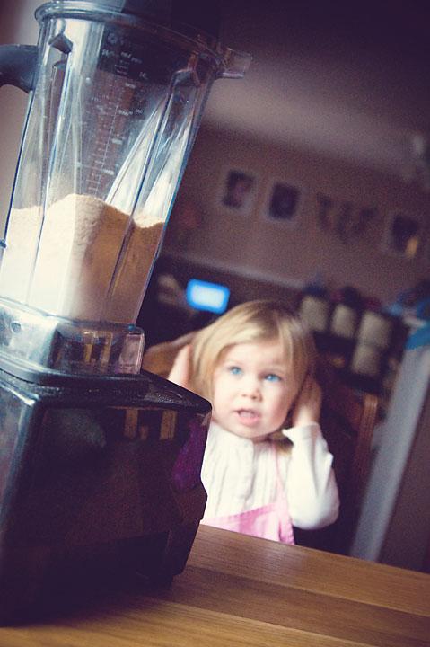 little girl covering her ears because of blender