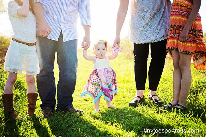little girl holding hands of her family
