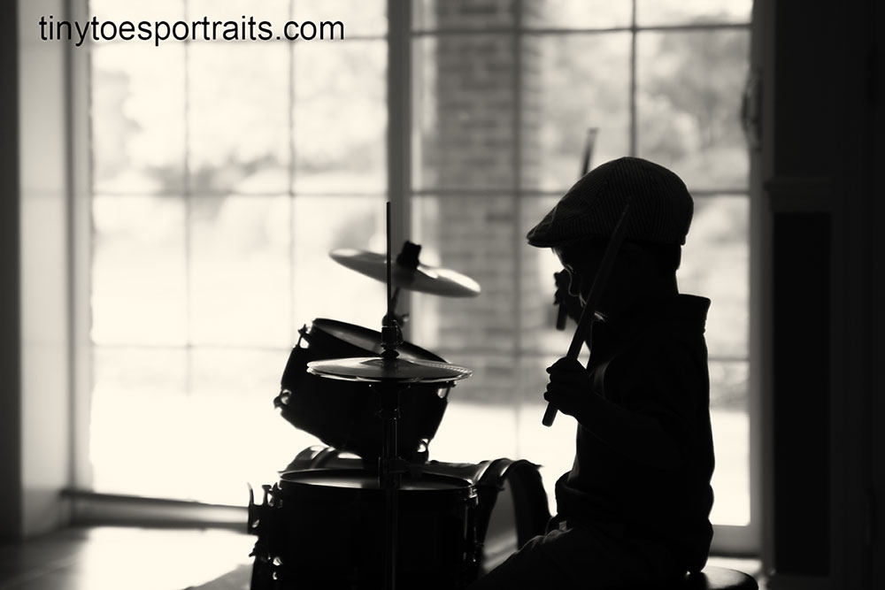 silhouette of little boy playing the drums