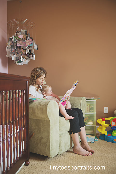 mom reading a book to her baby girl