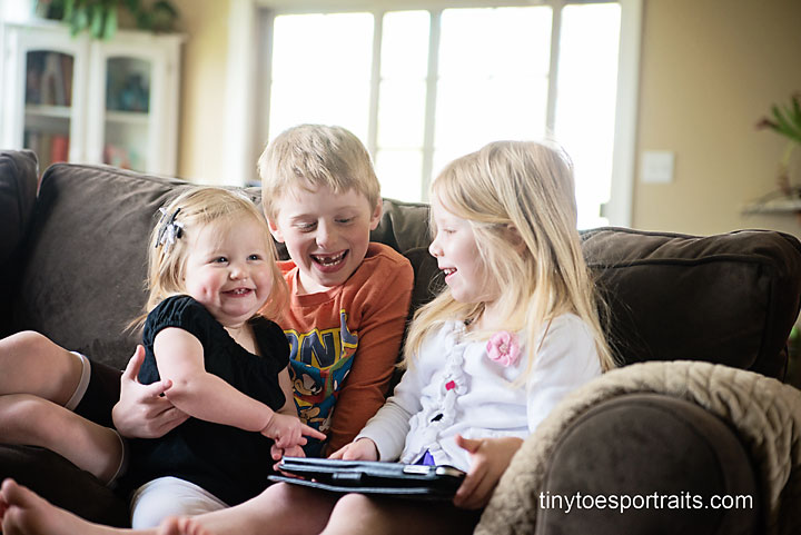 three kids giggling and watching the ipad
