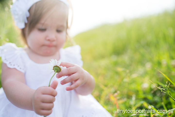 baby girl looking at flower