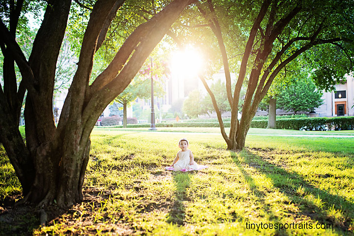 baby girl at sunset on the grass at the cathedral of learning