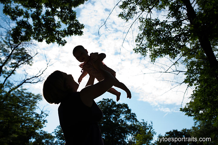 mom holding baby in air in silhouette