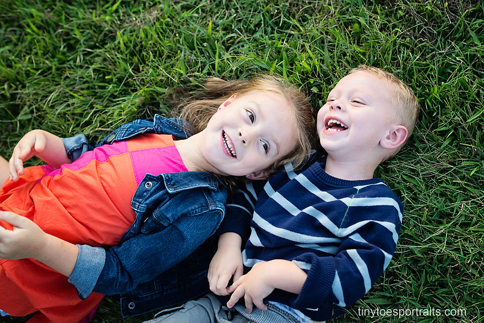 brother and sister laughing in the grass