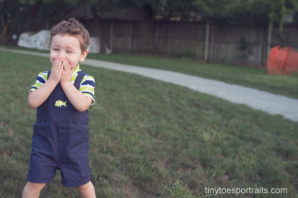 little boy covering his mouth in joy