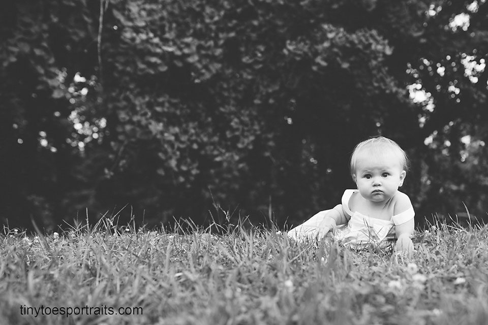baby girl sitting in the grass black and white