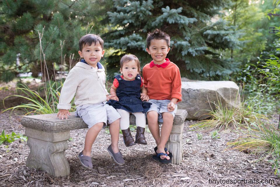 three little kids sitting on a bench
