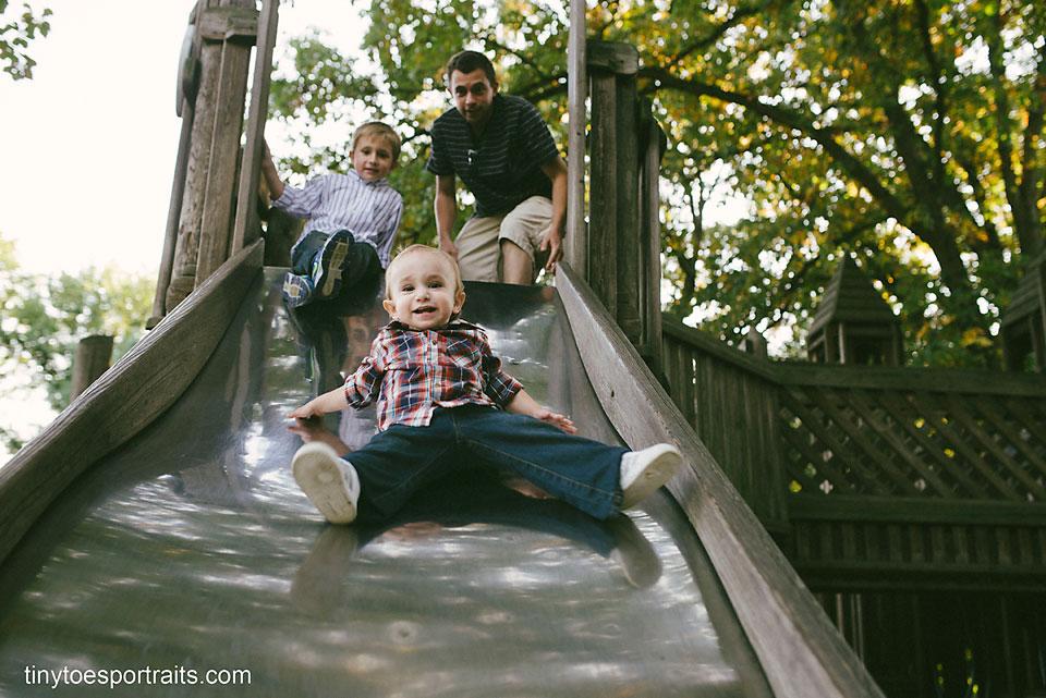 baby boy going down a slide