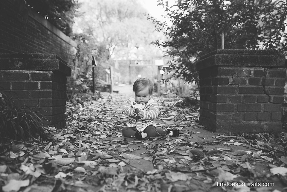baby girl playing with leaves