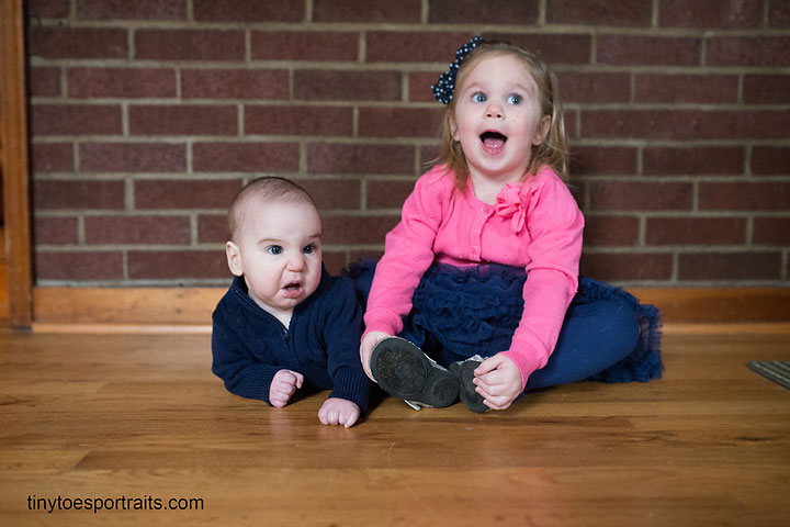 brother and sister on wooden floor