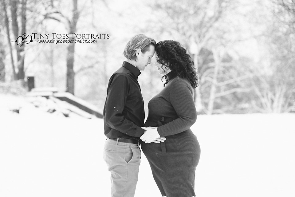 pregnant woman and husband touching heads in a snowy field