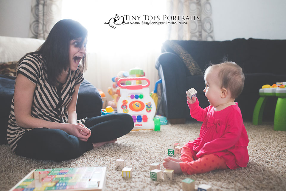 baby girl and her mom laughing at a block