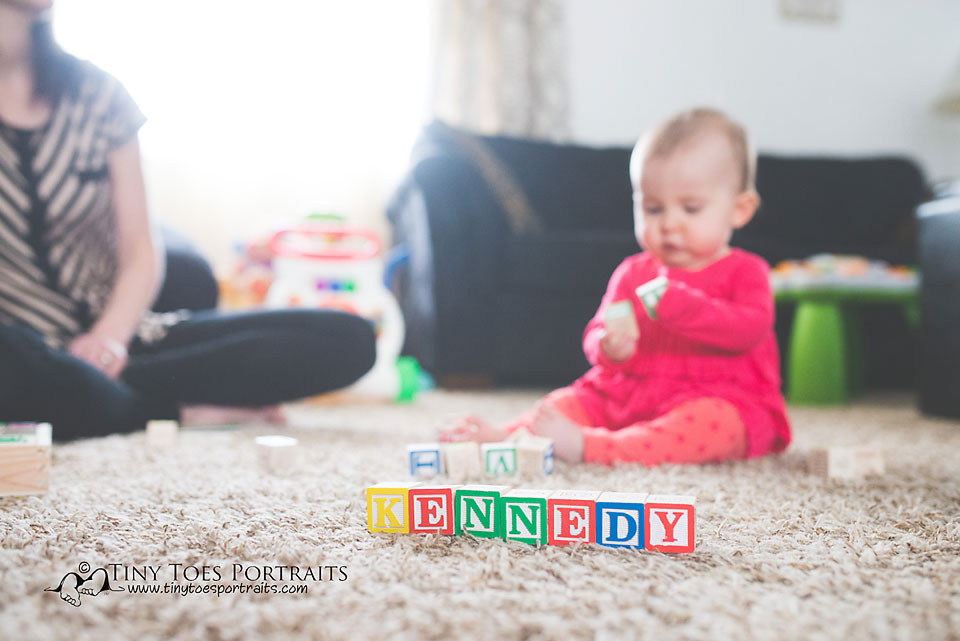 baby girl with blocks spelling her name