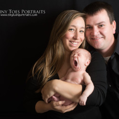 mommy, daddy, and yawning baby on black backdrop