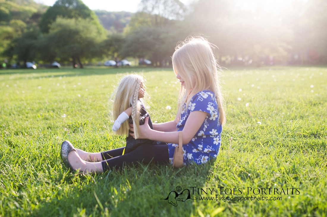 young girl playing with her american girl doll
