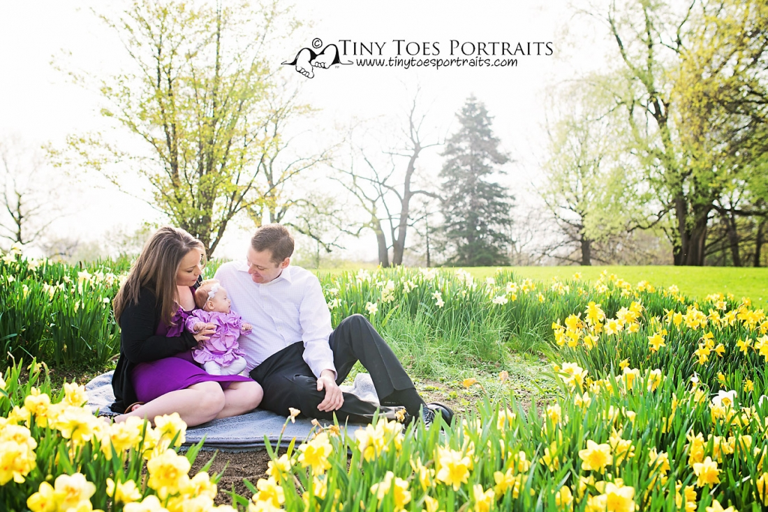 mom, dad, and baby sitting in the flowers
