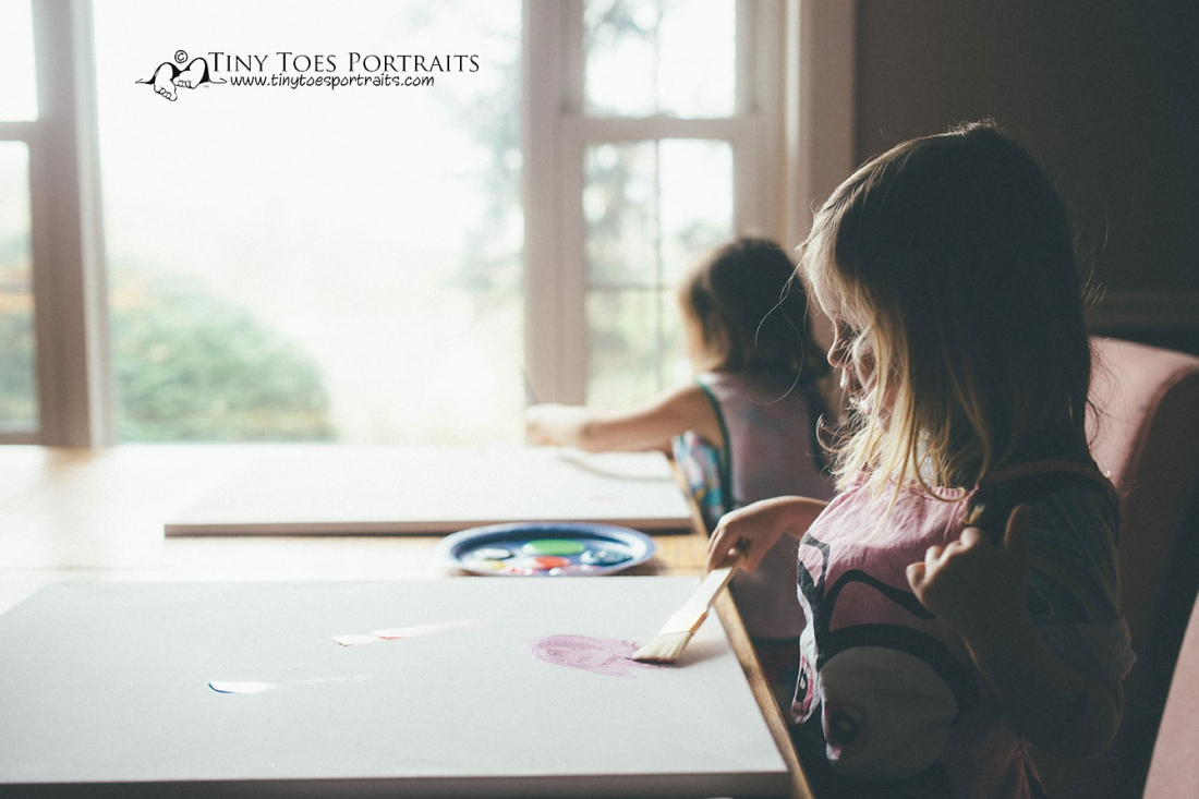 two little girls painting pictures at the table