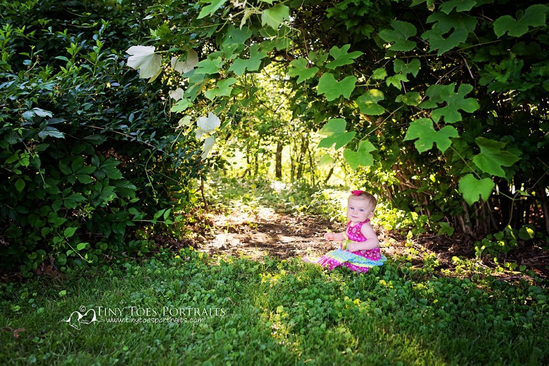 baby girl sitting by the trees