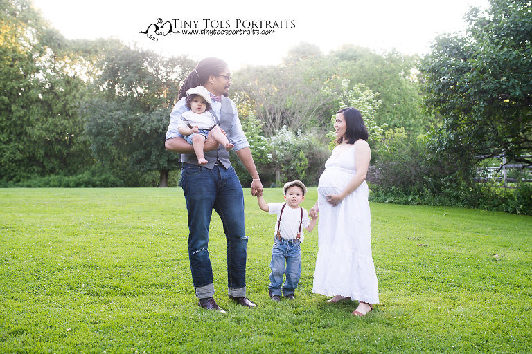 family of four with a pregnant mom standing in a field