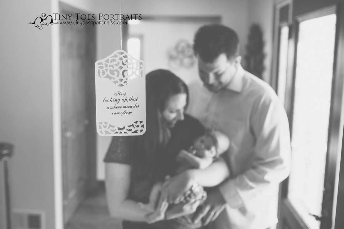 parents holding their baby girl with a quote in the front