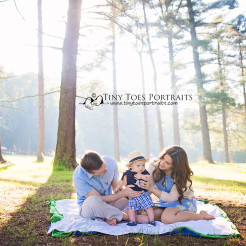 family of three sitting on a blanket in the trees