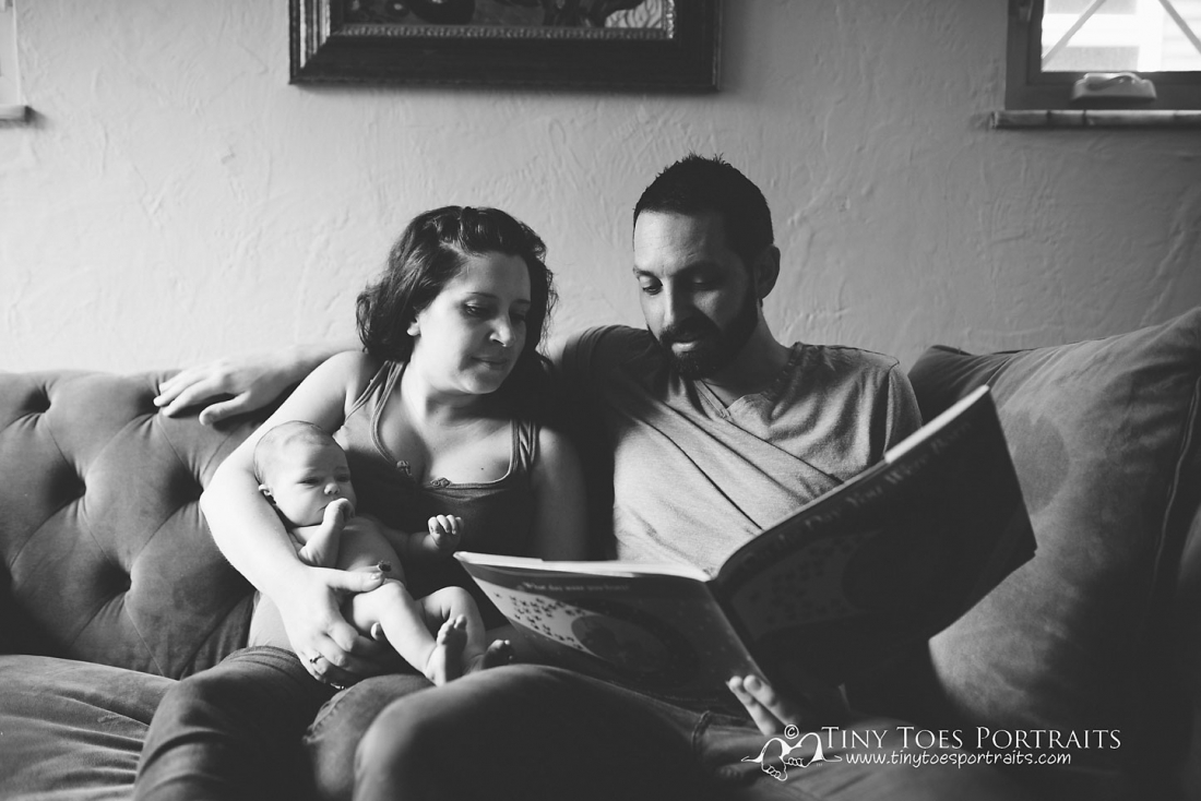 mom and dad cuddling with newborn baby girl on the couch