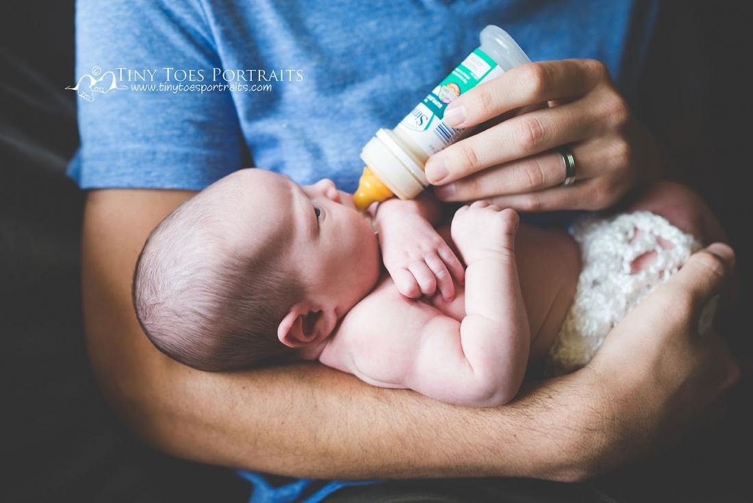dad feeding newborn baby a bottle
