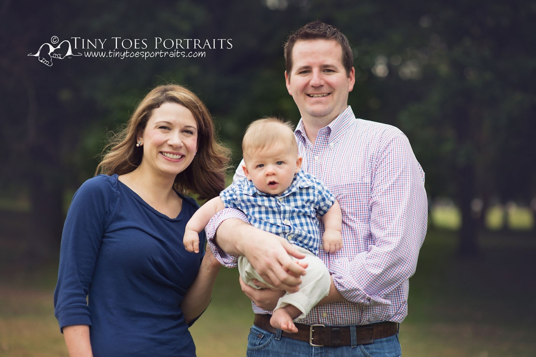 family of three smiling at camera