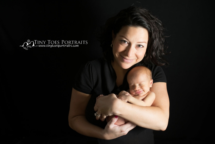 newborn girl with mom on black backdrop