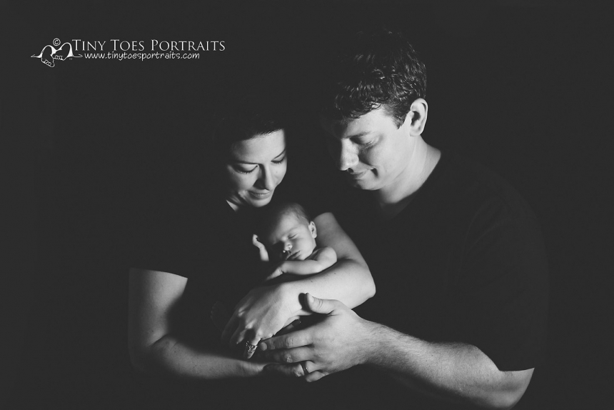 mom and dad holding newborn girl in black and white
