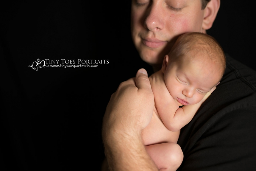 newborn girl with dad on black backdrop
