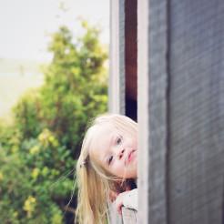 little girl peeking out the window
