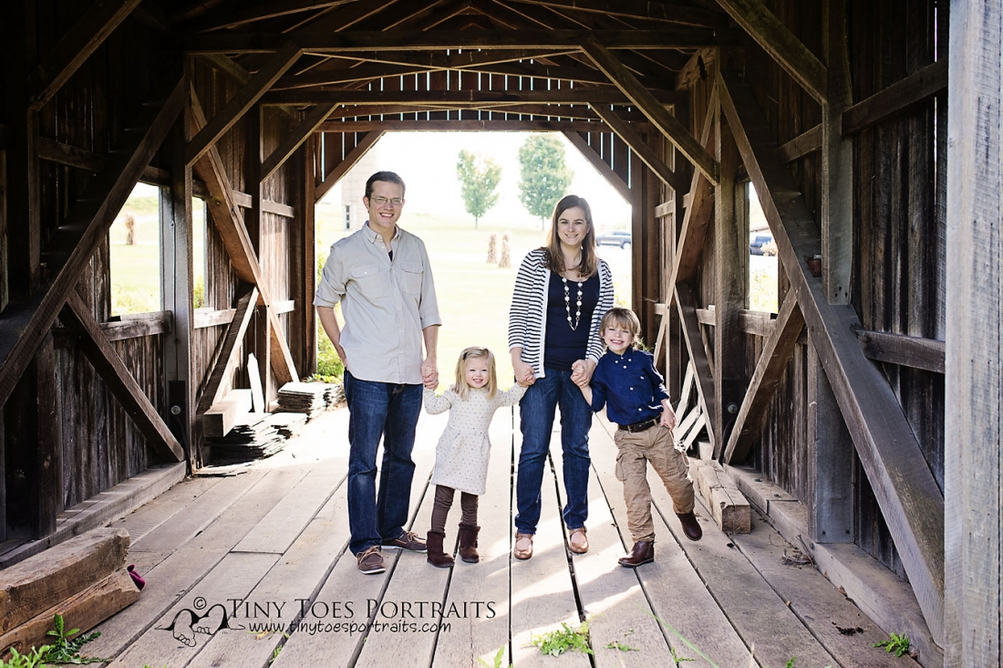 family of four standing in a covered bridge