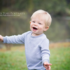 little boy laughing in a field