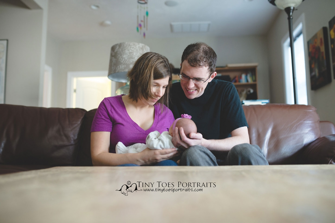 newborn girl being held by her parents