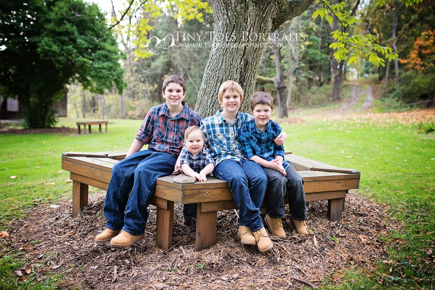 four brothers sitting on a bench