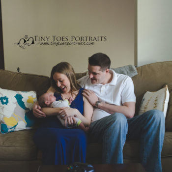 newborn boy with parents on the couch