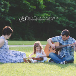 family playing the guitar outside