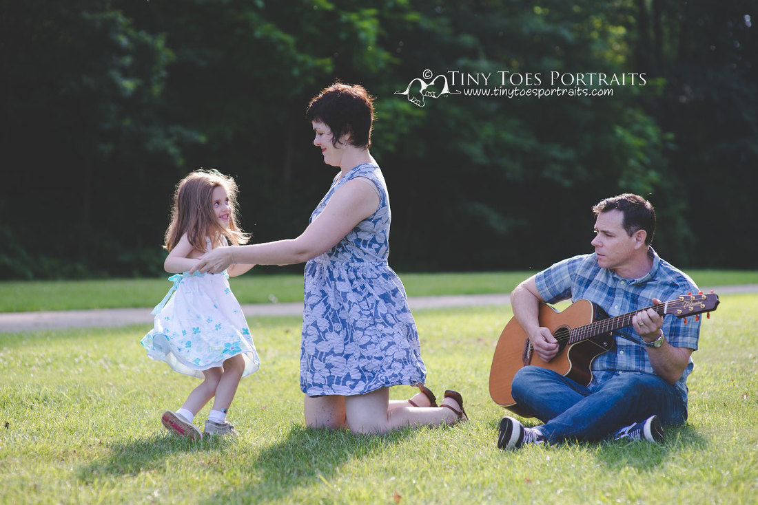 mom and daughter dancing while dad plays the guitar