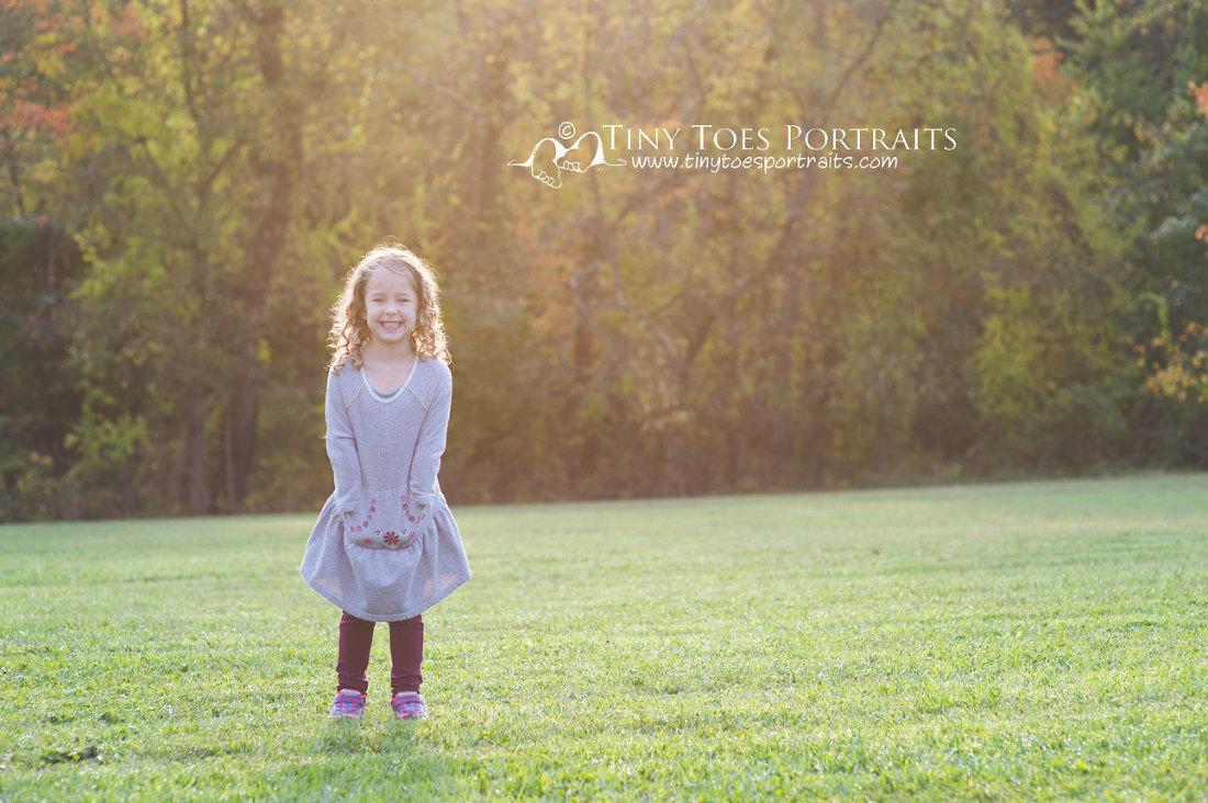 little girl standing in a field