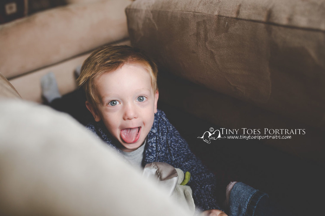 little boy sticking his tongue out at the camera