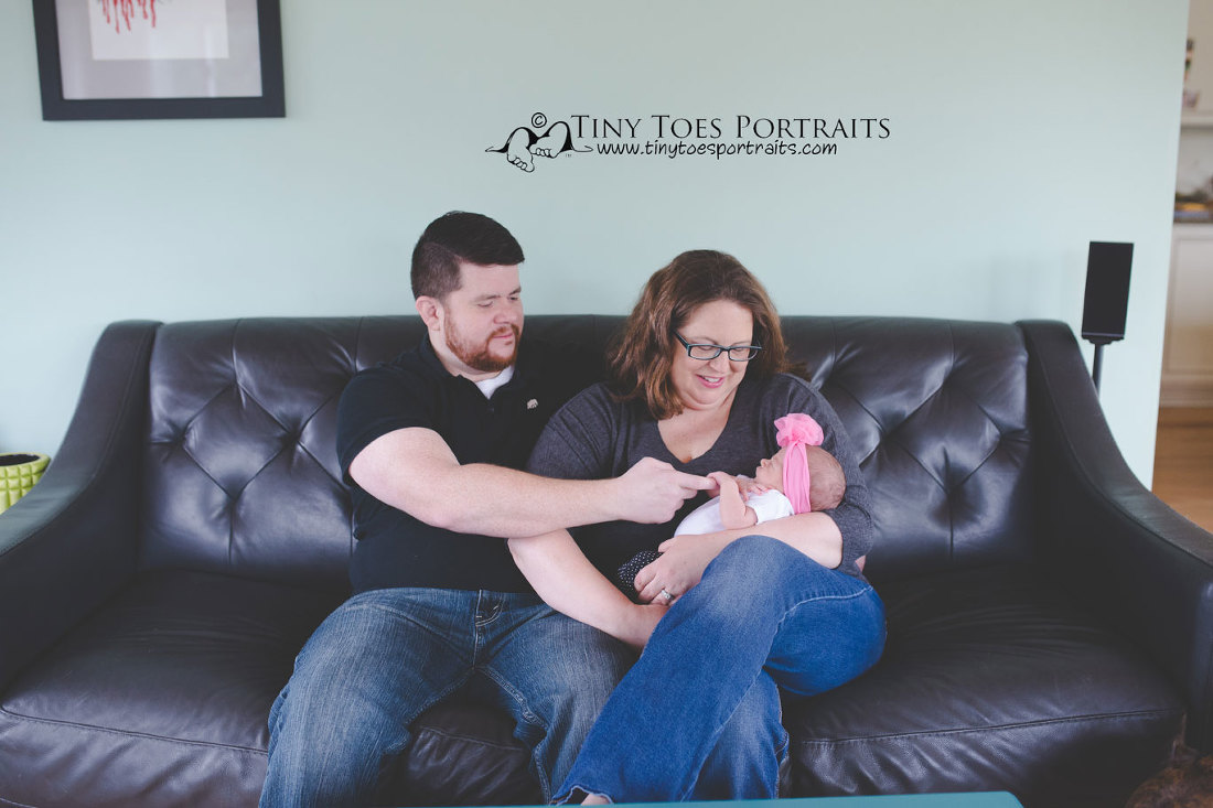 mom and dad with newborn girl on couch
