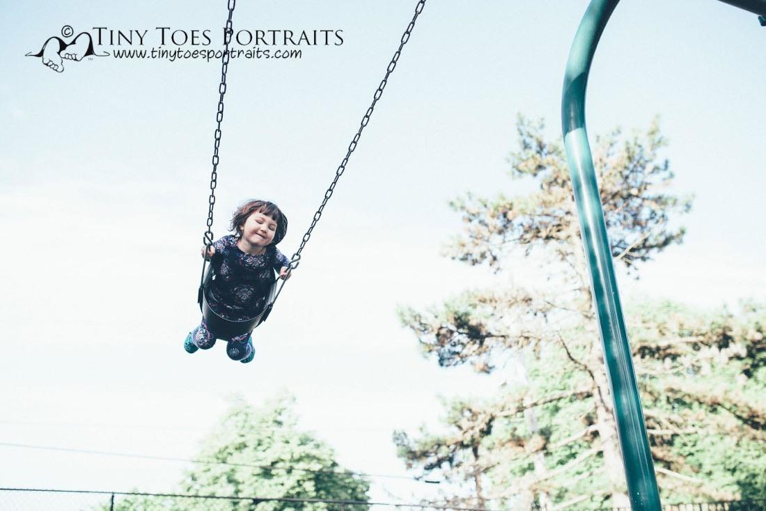 little girl swinging high