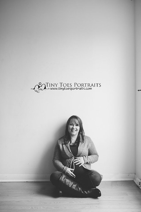 pregnant woman sitting against a white wall in black and white