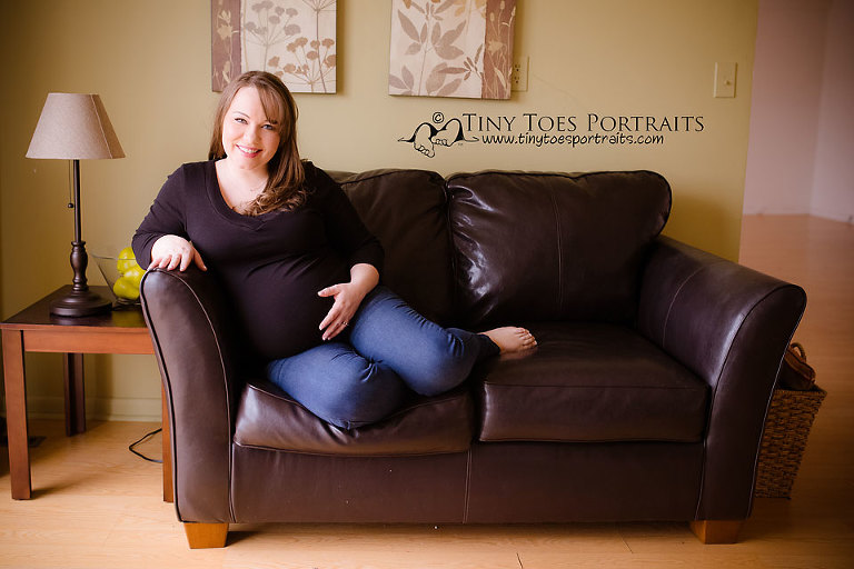pregnant woman sitting on a black couch